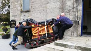 Piano festival volunteers lifting a Steinway piano into St Mary's Church last weekend.