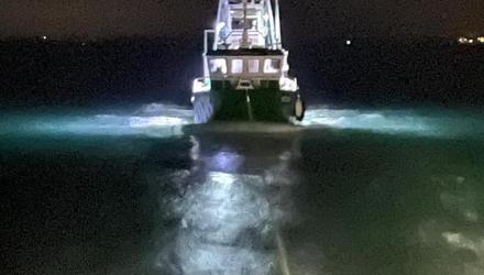 The fishing vessel being towed to safety.