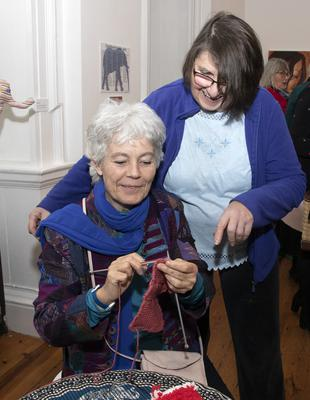 Bridget Sheeran knitting while Mary Smyth watches on at the opening of 'Picking up the Threads: Remaking the Fabric of Care', an exhibition of work by the Elephant Collective in Wexford Arts Centre