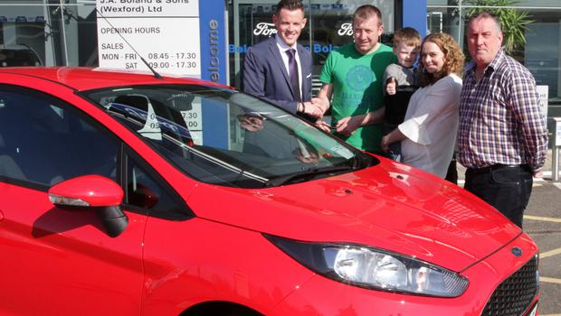 Cathal Murphy hands over the keys of a brand new Ford Fiesta to JP Furlong from Cloughbawn with his wife Joanne and son Michael along with Dessie Doyle, chairman of Adamstown GAA Club.