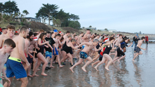 GO! The Rosslare swimmers race to the water on Christmas Day