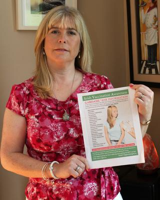 Susan Whitmore with a pamphlet that makes claims about the vaccine.
