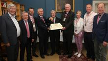 Tony Dempsey, Brendan Howlin TD, Sean Foley, Robert O'Callaghan, Dr Bart Curtis cutting the anniversary cake, David Power, Mairead Colman, Declan Cloney and Pat Quigley