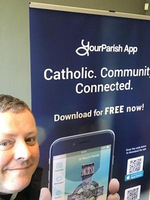 Fr. John Carroll pictured with the promotional banner for the app