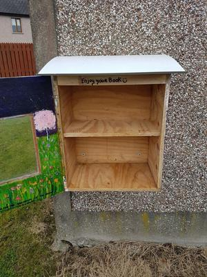 Young readers Darragh Scallan and Amy Hatchell make a plea to the thief. The well-stocked Little Free Library (left) was left bare (above).
