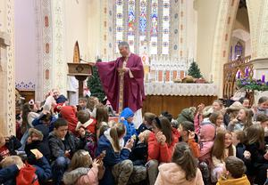 Fr John Carroll blesses the figurines of the baby Jesus brought by local children on 'Bambinelli Sunday'