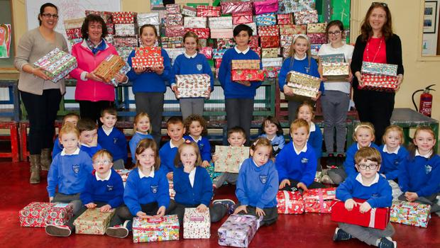 Pupils of Rathangan NS with their collection of Christmas shoe boxes, with Annette Doran of the Christmas Shoe Box Appeal, Nichola Roche, principal, and Sinead McCoy, teacher