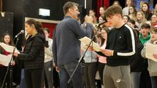 Lead singers Ciara Doherty and Josh Walsh with conductor Liam Bates (centre) during rehearsals.
