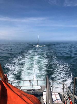 The yacht being towed back to shore by Rosslare RNLI