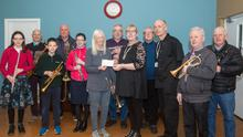 Members of the HFC Band present the cheque to Oznam House