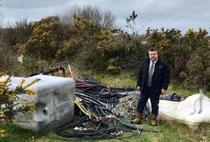 Cllr George Lawlor with the rubbish dumped at Pairc Charman last week