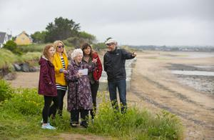 93-year-old local resident Nancy Dempsey shows artists Mark Clare, Fiona McDonald and Mary Conroy and Joanna Hopkins photos of how the area looked in the past at the launch of the unique public art project at Portrane beach