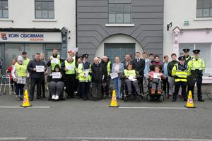 Wheelchair users with local representatives, Garda officers and supporters at Crescent Quay yesterday (Monday)