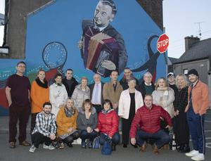 Artists who created the mural, pictured with members of the Ross family.