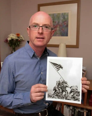 Local historian Stephen Foley with the iconic image from Mount Suribachi