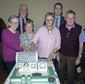 Mary Cassidy, who was one of the first students in the Technical School, Peggy Jones (Tops Group), Ann McMorris (Hall Commitee) and Seamus O'Keeffe, with councillors Jim Moore and Ger Carthy cutting the cake model of the hall made by Lorraine Rankin