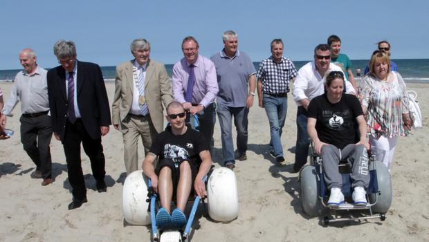 Chairman of Wexford County Council  Cllr Tony Dempsey launched the beach wheelchairs at Curracloe beach with the help of wheelchair users Dan Morris, Amy Fitzpatrick and John Horan, councillors and county council officials.
