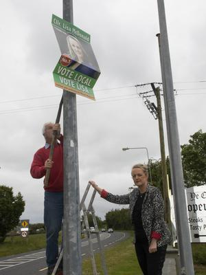 Cllr Lisa McDonald and her father Eddie removing a poster from a pole on the Rosslare Road at Drinagh