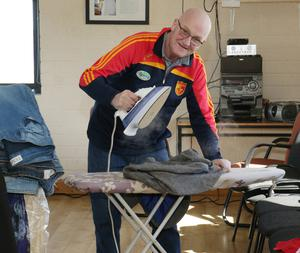 Frank Clancy does a spot of ironing at the sale of Wexford Variety Group props and costumes in the Sarsfields' clubhouse.