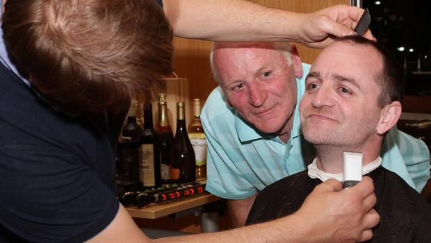 Shane O'Neill has his beard chopped off by Joe The Barber. Left: the finishing touches are applied, under the watchful eye of Shane's dad Larry.