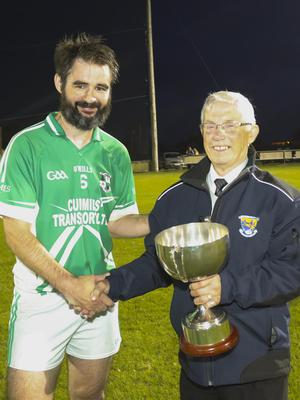 St. James' captain Brian Kennedy receives the cup from Mick Bowe.