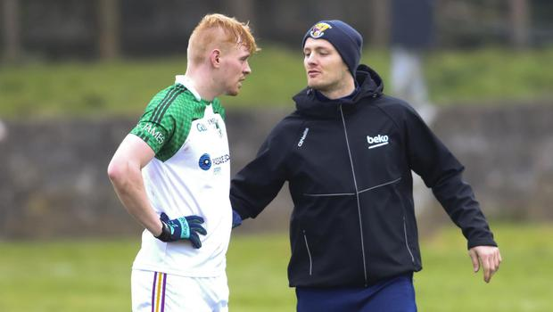 Matthew O'Hanlon giving some half-time encouragement to his St. James' clubmate, Darragh Lyons, before the resumption of their Tom Doyle Supplies SFC clash with Gusserane in O'Kennedy Park, New Ross, on Saturday. St. James' lost by 0-13 to 0-12