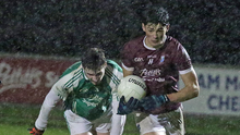 Barry O'Connor of St. Martin's races away from Jack Cushe (Naomh Eanna) in the pouring rain