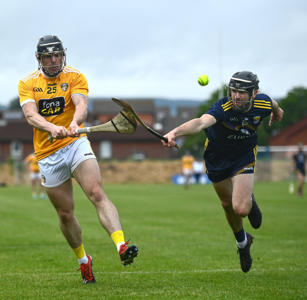 Antrim substitute Ciarán Clarke picking off a second-half point despite the best efforts of Wexford's Connal Flood. Photos by Sportsfile