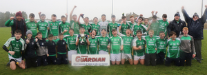 The Naomh Eanna squad singing in the rain after completing the double-double in Enniscorthy on Saturday