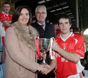 Yvonne Kavanagh (nee Donohoe) presents the Tom Donohoe Memorial Cup to Niall O'Reilly of Monageer-Boolavogue as Co. Chairman Diarmuid Devereux looks on