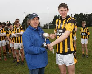 Darragh Howlin receives the cup from James Mullally