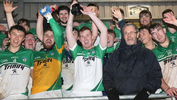 Non-playing Cloughbawn captain Lee Keeley raises the cup after receiving it from Rory Murphy