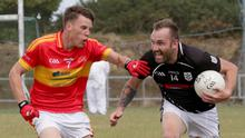 Andy Moore of St. Joseph's is challenged by Horeswood defender Seán Stafford