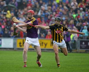 Wexford centre-back Mike Kelly attempts to clear as Niall Brassil applies pressure