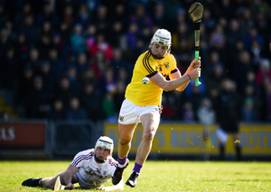 Wexford's Rory O'Connor takes aim for the posts as a grounded Jack Coyne of Galway looks on