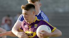 Wexford captain Ciarán Kavanagh is tackled by Seán Michael Corcoran of Laois during Wednesday's encounter