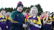 Aisling Byrne, the Presentation captain, is presented with the cup by Brendan Cahill of the Leinster Schools Camogie Council