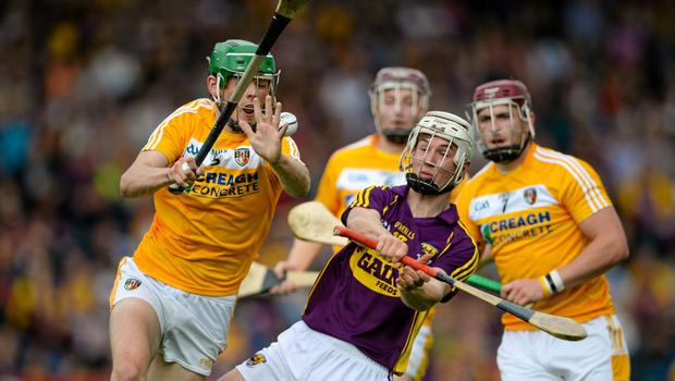 Cathal Dunbar runs out of room as Gerard Walsh from Antrim applies heavy pressure