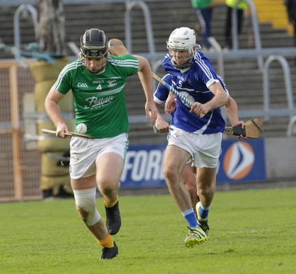 Eoin Molloy of Naomh Eanna bursts out of defence as Ciarán Hourihane gives chase