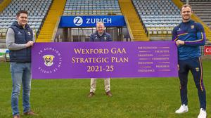 Shane Roche, Micheál Martin and Matthew O'Hanlon with a sign outlining the themes explored in Ar Aghaidh Le Chéile, Wexford GAA's five-year strategic plan for 2021 to 2025