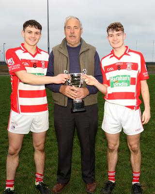 Joint captains Mark Doyle and Jamie Thomas receiving the trophy from Seamus Whelan