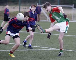 Tomás Mythen blasts the ball to the net past St. Colmcille's defender Scott Cramer-Walsh