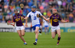 Austin Gleeson about to bat the ball off the ground as Eanna Martin and Diarmuid O'Keeffe give chase