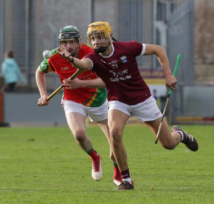 Harry O'Connor of St. Martin's off-loads as Rapparees defender James Peare looks on