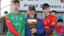 Joint captains Anto Larkin and Lee Jordan accepting the Jim Byrne Cup from James Mullally