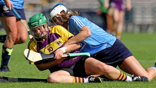 Wexford's Stacey Kehoe goes to ground and grimaces after this strong challenge from Aoife Woods of Dublin