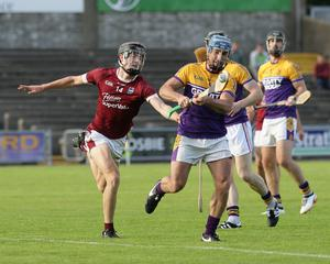 Brendan Mulligan (Faythe Harriers) clears as Joe O'Connor (St. Martin's) attempts the hook