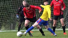 Craig Parker of Curracloe United nicks the ball away from Sam Wall of St. Leonards