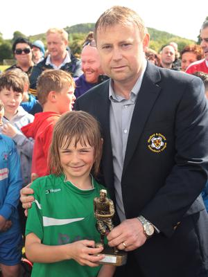 Thomas Cowman presents the player of the match trophy to Shayne McDonald, Cloughbawn