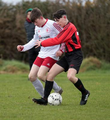 Kyle Kenny (Gorey Rangers) is tackled by Pierce McDonnell